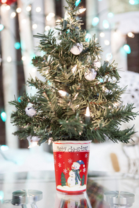 A miniature Christmas tree with lights and silver decorations in a red mug that says Merry Christmas with a snowman on it.