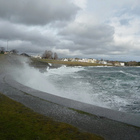 Ocean waves crashing high onto a breakwater in a Victoria neighbourhood on a cloudy, stormy day.