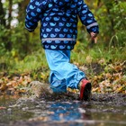A young child from the shoulders down in a blue raincoat, blue splash pants, and red boots, sloshing through a puddle on a forest trail. Credit to magentapix on Pixabay.