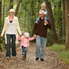 A family of four with two young children, taking a walk through the woods.