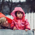 Mother smiling at her young daughter peering over a wooden fence, both wearing rain jackets.