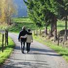 A senior couple walking down a park road with their arms around each other.