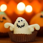 A cupcake styled in the shape of a googly-eyed ghost, with two smiling pumpkin-shaped cupcakes behind it.