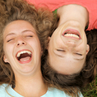 Two laughing teenage girls lying with their heads side-by-side on their backs in the grass.